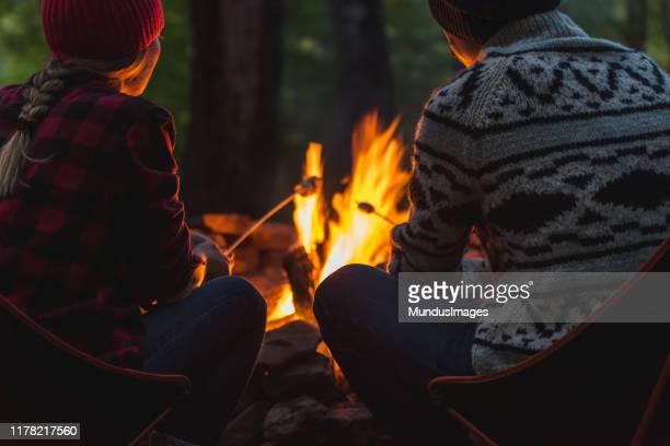 カップルのローストマシュマロ - キャンプファイヤー ストックフォトと画像