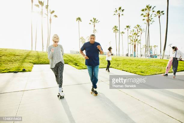 couple roller skating together in park - skate sports footwear stock pictures, royalty-free photos & images