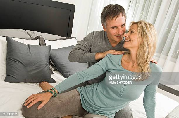 couple romancing in a bedroom - husband massage wife stock photos and pictures