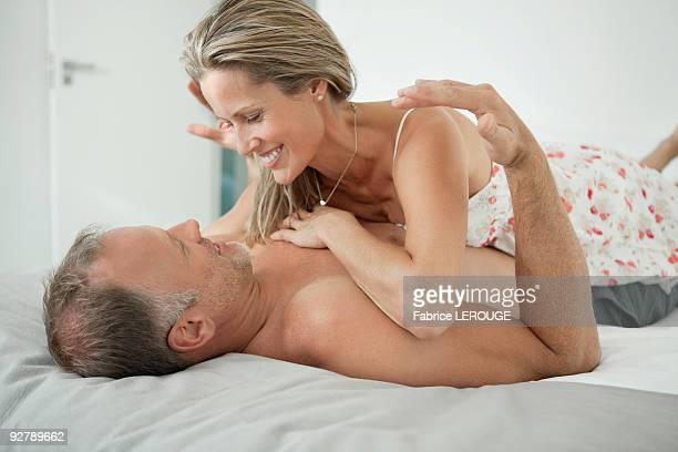 couple romancing on the bed - geschlechtsverkehr stock-fotos und bilder