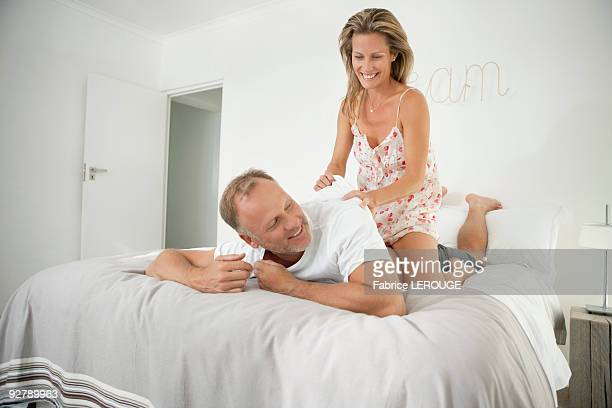 couple romancing on the bed - women in slips stock photos and pictures