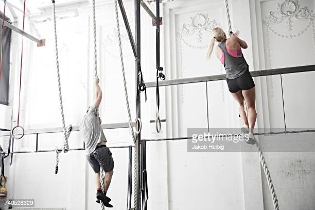 Couple rope climbing in cross training gym