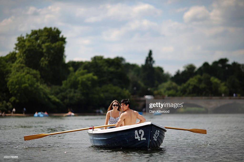A couple row a boat across the Serpentine in Hyde Park on July 17, 2014 in London, England. The Met Office has issued a heatwave alert as temperatures throughout England and Wales are predicted to reach their highest level of the year this weekend.