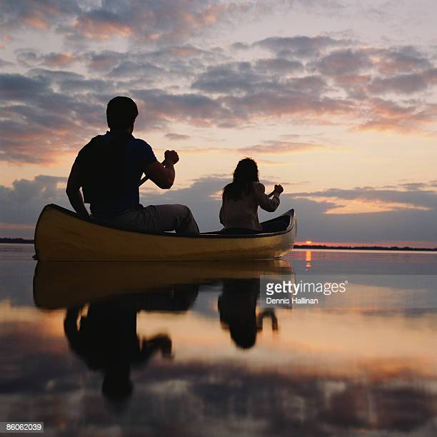 Couple rowing canoe in lake at sunset