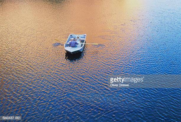 Couple rowing on lake, aerial view, orange reflection in water