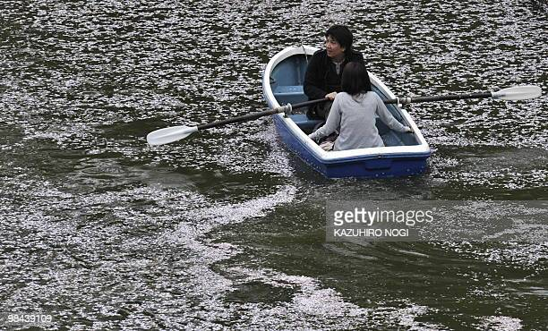 A couple rows their boat on a moat covered with cherry blossom pedals in Tokyo on April 11 2010 Japanese people all over the country enjoy the annual...
