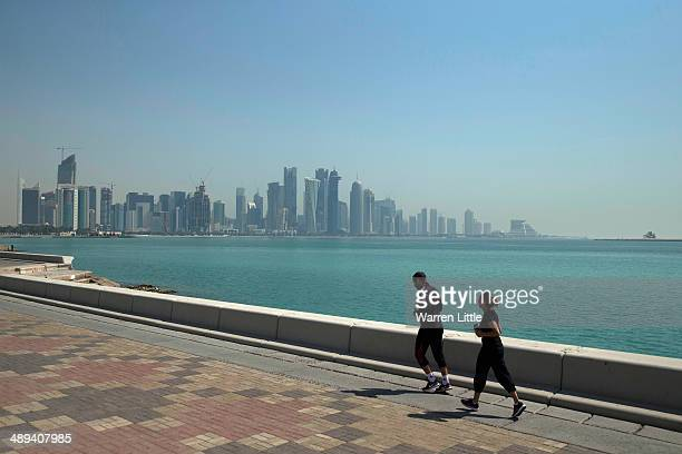A couple run along the corniche with Doha city in the back ground on May 9 2014 in Doha Qatar