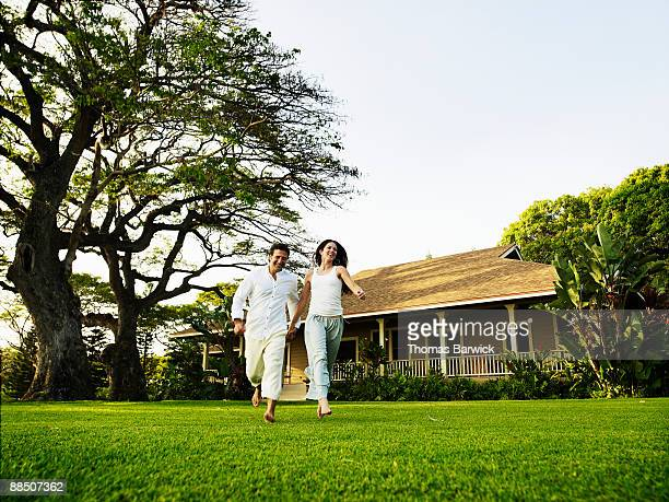 Couple running across front lawn of tropical home