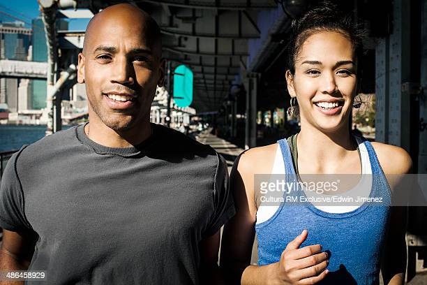 Couple running along waterfront, New York, USA