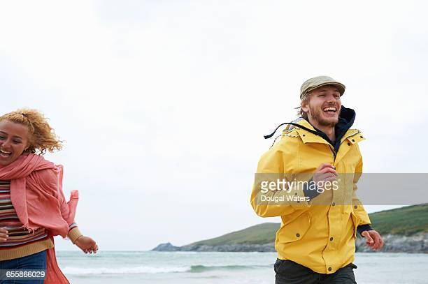 Couple running and laughing at beach.