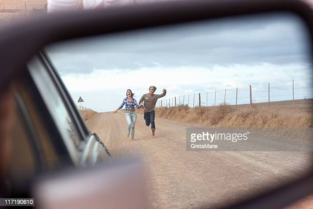 Couple running behind car