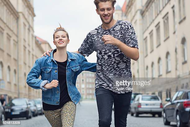 couple running happily through the city streets