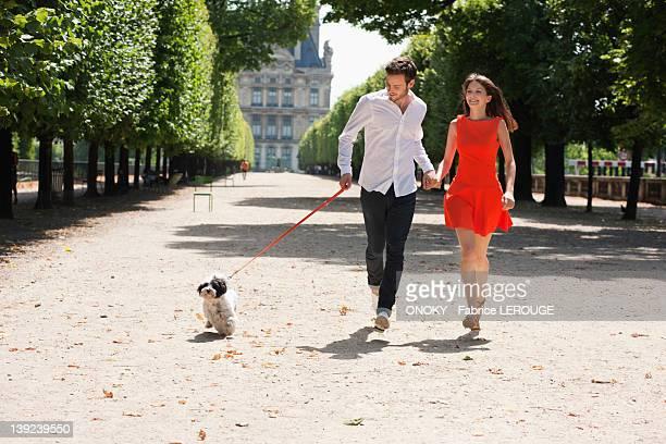 couple running in a garden with a puppy, terrasse de l'orangerie, jardin des tuileries, paris, ile-de-france, france - チュイルリー地区 ストックフォトと画像