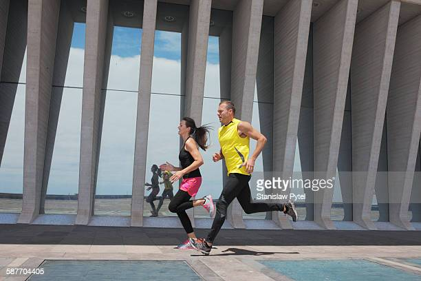 Couple running in colorful clothes in city