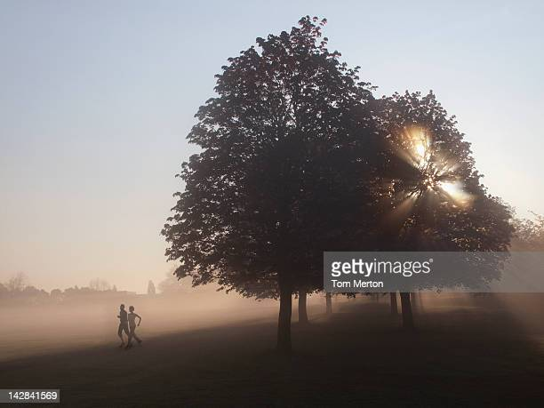 Couple running in foggy field