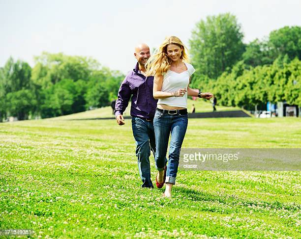 couple running in park, having fun - 40 49 jaar stockfoto's en -beelden