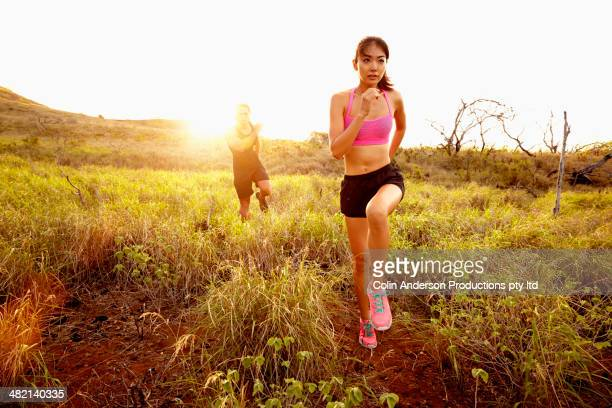 Couple running in rural field