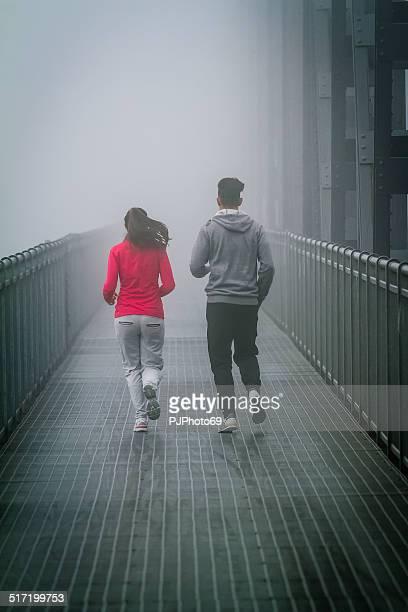 paar laufen im nebel auf iron bridge - pjphoto69 stock-fotos und bilder