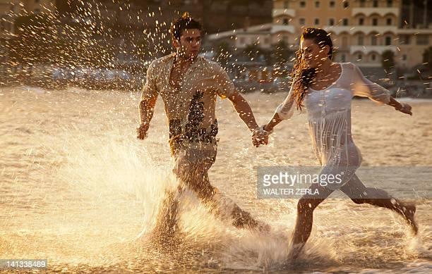coppia che corre in onde sulla spiaggia - liguria foto e immagini stock