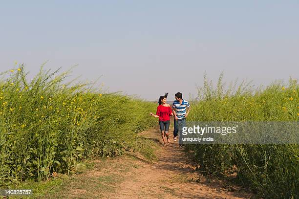 couple running near an oilseed rape field - crucifers stock pictures, royalty-free photos & images