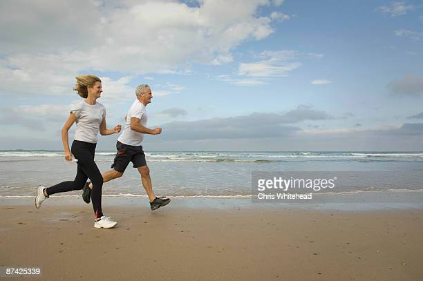 couple running on a beach - heterosexual couple imagens e fotografias de stock