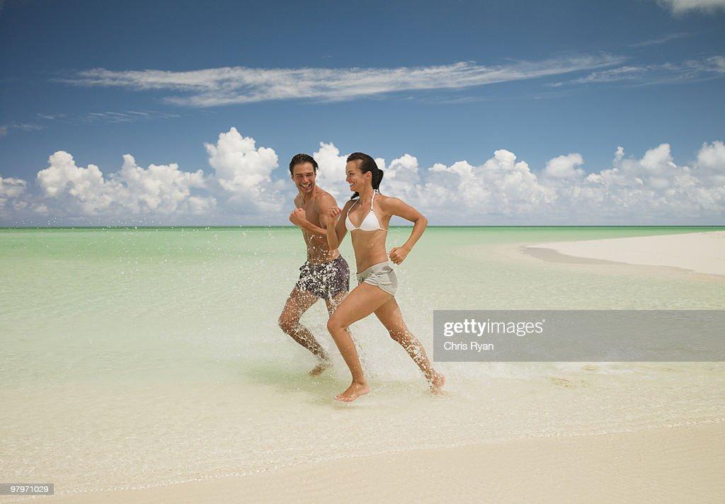 Couple running on beach and splashing in ocean : Stock Photo