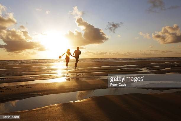 Couple running on beach at sunset