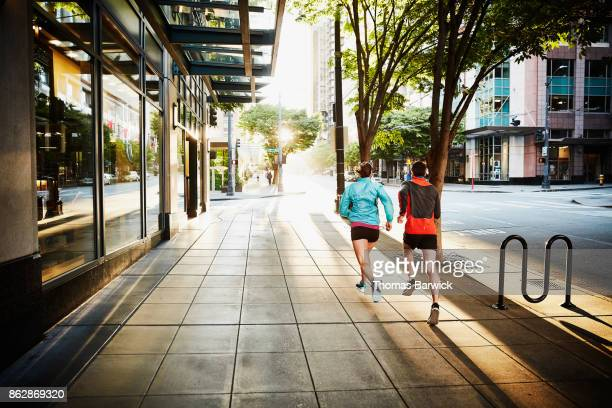 Couple running on city sidewalk during early morning workout