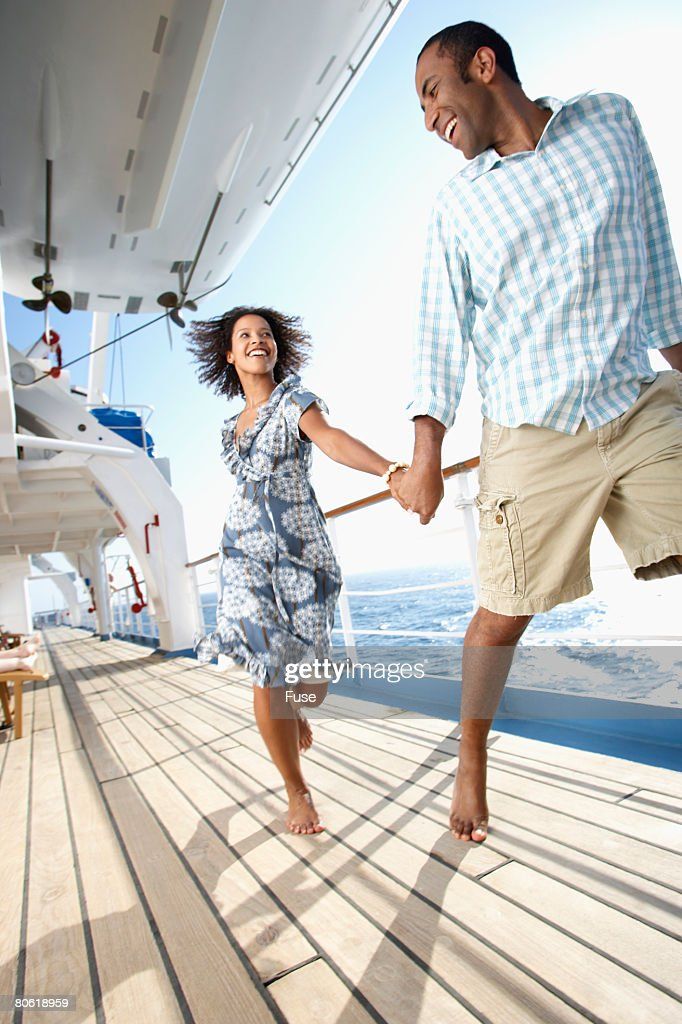 Couple Running On Cruise Ship Deck High-Res Stock Photo