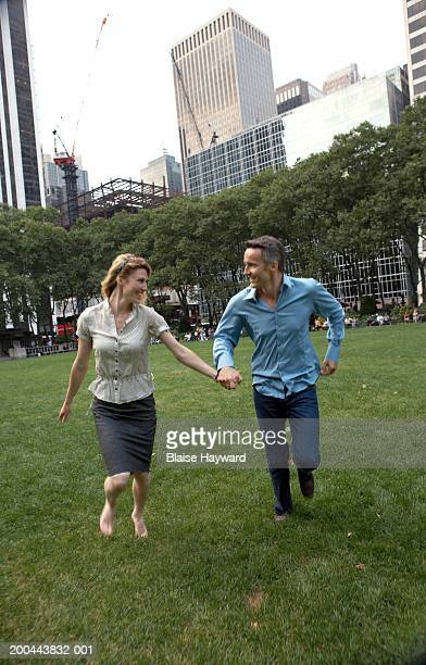 Couple running on lawn, looking at each other, smiling