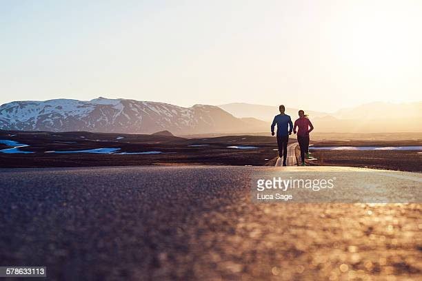 Couple running on road at sunrise in the mountains