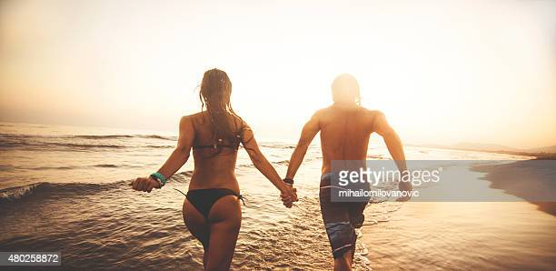 couple running on the beach - hot love stock pictures, royalty-free photos & images
