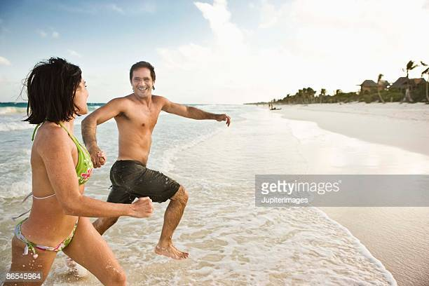 couple running on the shore - playa del carmen stock pictures, royalty-free photos & images