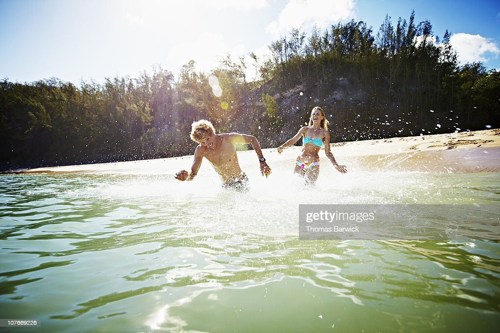 Couple running out into water laughing : Foto de stock