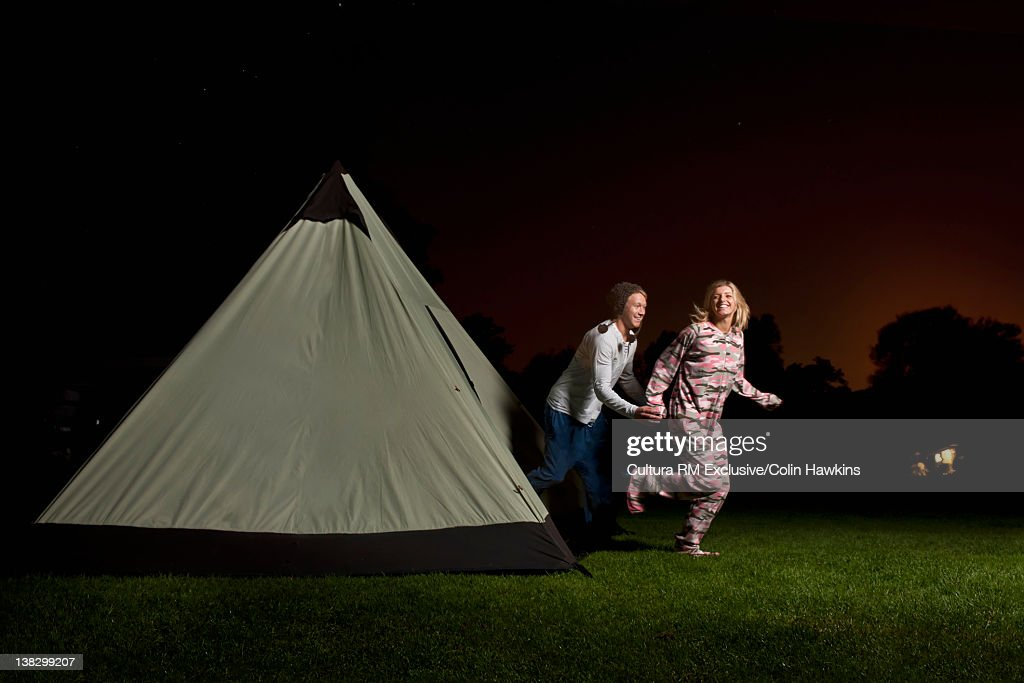 Couple running out of tent at campsite : Stock Photo