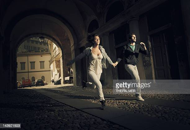 couple running scare - escapism stock pictures, royalty-free photos & images