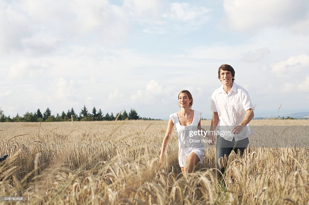 Couple Running Through Field : Stock Photo
