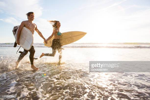 Couple de jogging à travers le surf