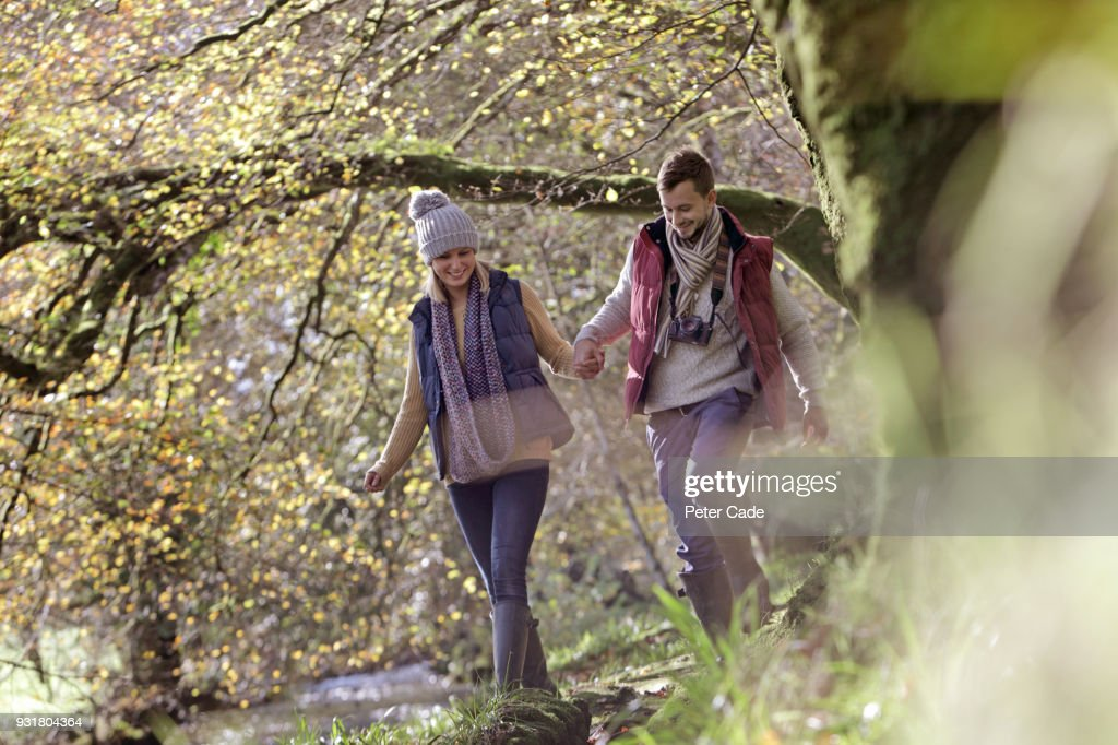 Couple running through woodland next to river : Stock Photo