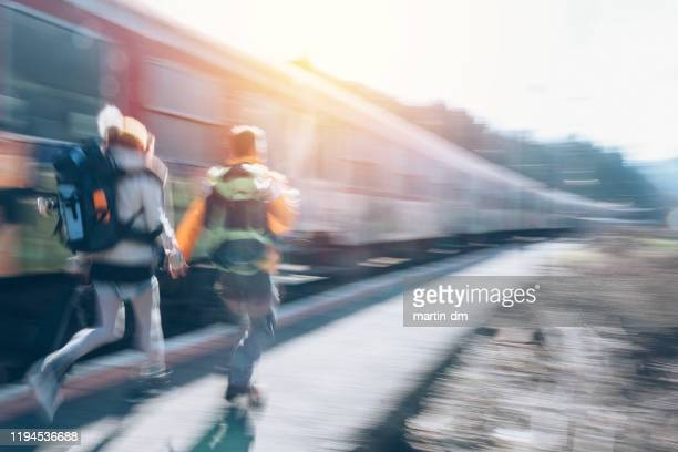 couple running to get on the train - martin dm stock pictures, royalty-free photos & images