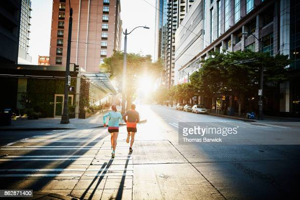 Couple running together on empty city street during workout at sunrise
