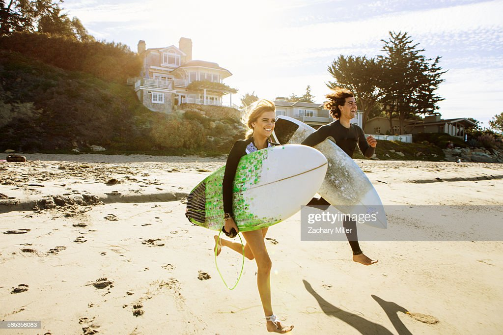 Couple running towards sea, carrying surfboards : Stock Photo