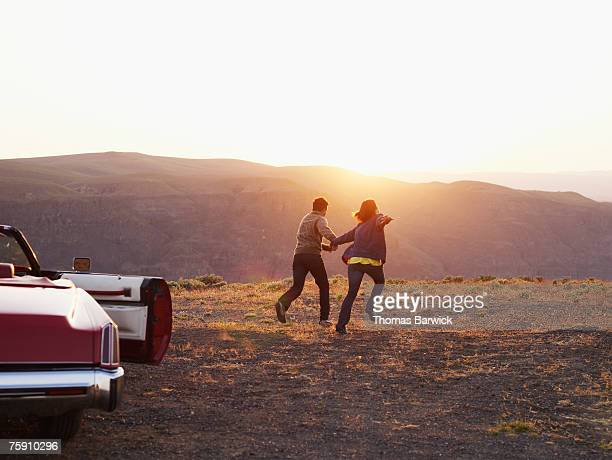 Couple running towards sunset, convertible with door open in foreground