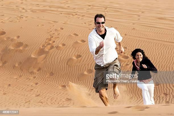 Couple running up desert dune