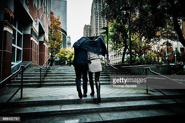 Couple running up stairs holding coat over head