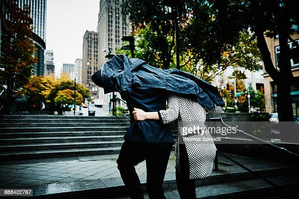 couple running up stairs with coat over head - affectionate stock pictures, royalty-free photos & images