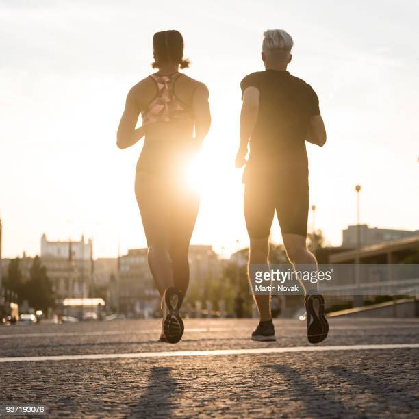 Couple running with sun in the background