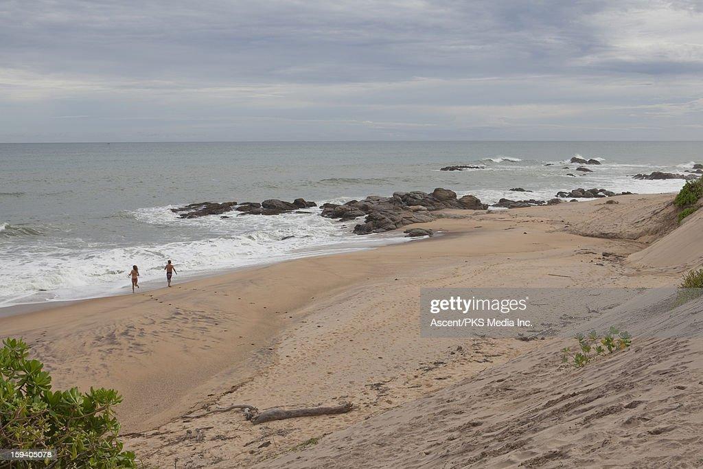 Couple runs into surf from empty beach : ストックフォト