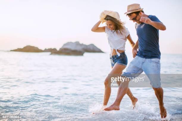 couple runs through waves - greece stock photos and pictures