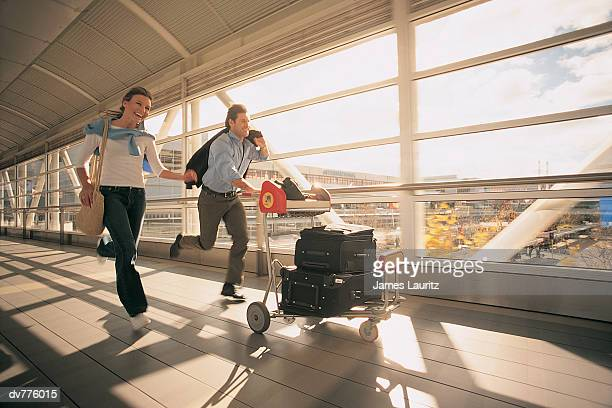 Couple Rushing Down a Corridor at the Airport, Pushing a Baggage Trolley